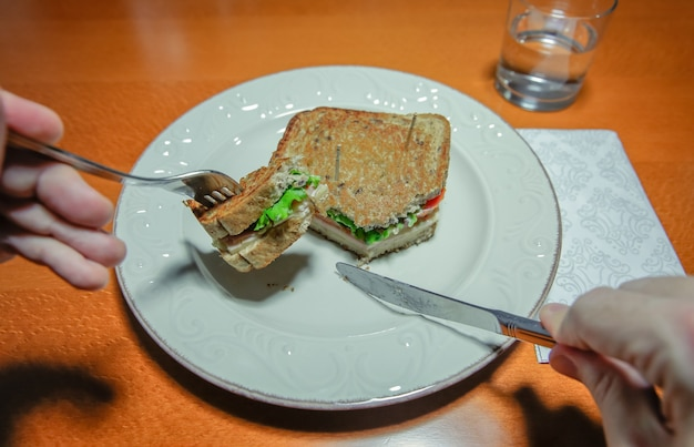 나무 테이블 위에 접시에 제공되는 포크와 나이프로 샌드위치를 자르는 남자 손의 클로즈업