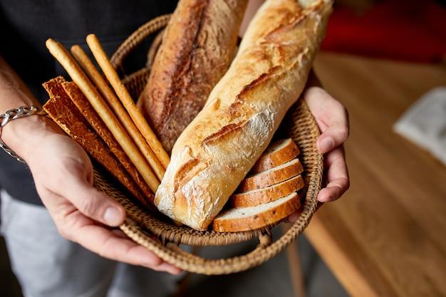 Крупным планом мужчина держит корзину с различным свежеиспеченным хлебом