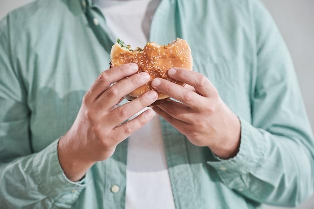 점심을 먹기 위해 손에 햄버거를 들고 있는 남자의 근접 촬영