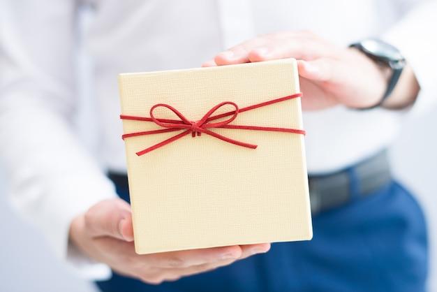 Крупным планом мужчина держит подарочную коробку