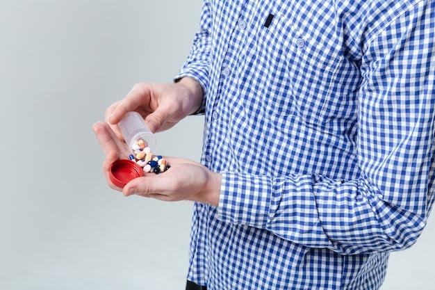 Крупным планом мужчина в клетчатой рубашке принимает таблетки из бутылки над белой стеной