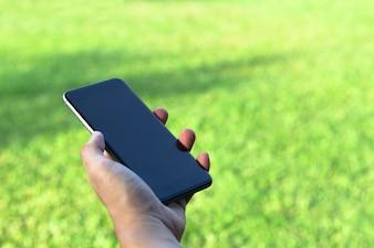 スマートフォンを持ち、屋外の公園に空のスクリーンを使用している男の手の拡大写真