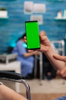 격리된 디스플레이가 있는 모의 녹색 화면 크로마 키를 보고 있는 남자 사회 복지사의 클로즈업