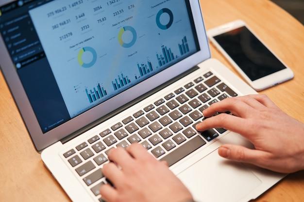 財政またはceo、グラフ、ビジネス分析および戦略でラップトップに取り組んでいる男のクローズアップ