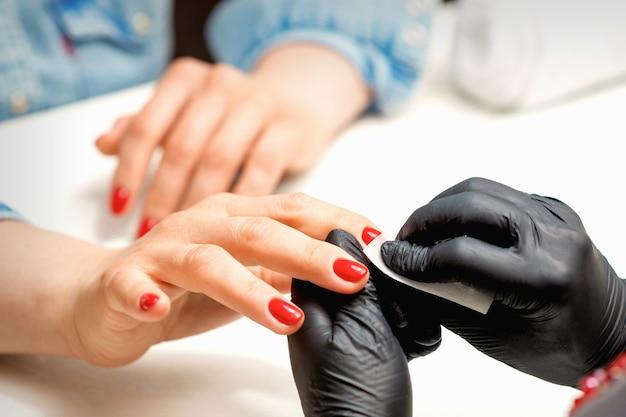 Крупный план мастера маникюра в черных перчатках, протирающего женские красные ногти бумажной салфеткой в салоне красоты