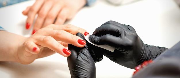 뷰티 살롱에서 종이 냅킨으로 여성 빨간 손톱을 닦아 검은 장갑에 매니큐어 마스터의 근접 촬영