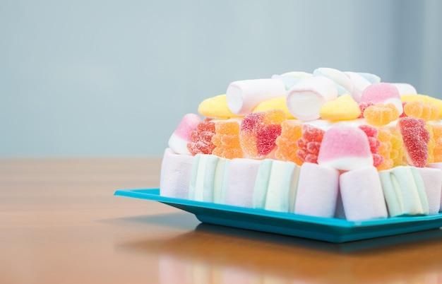 Крупным планом торт зефир и мармелад на синей тарелке для детской вечеринки в мягких пастельных тонах