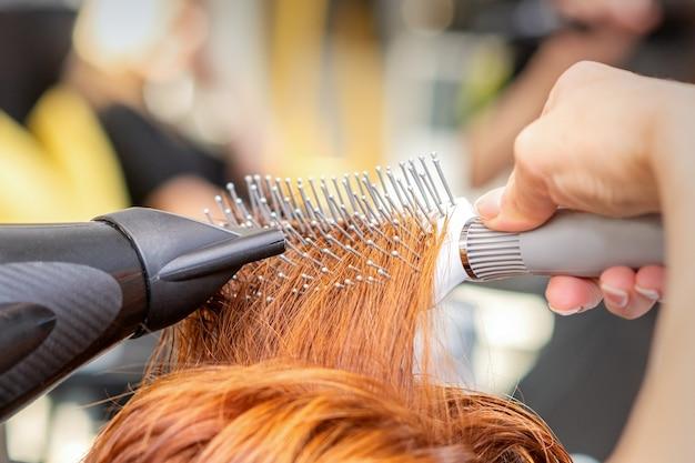 Крупный план хозяйской руки с феном и расческой дует женские рыжие волосы в салоне.