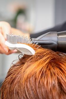 Blowdrying 및 헤어 브러시 살롱에서 여성 빨간 머리를 불고 마스터의 손의 근접 촬영