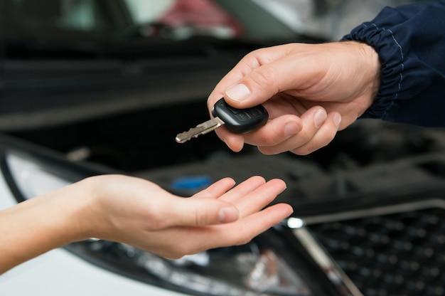 Крупным планом механик дает ключ от машины клиенту в гараже