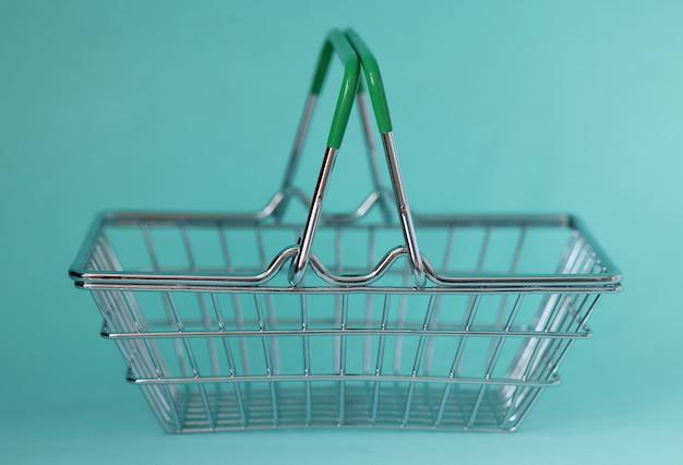 青い背景の上の金属の食料品バスケットのクローズアップ。ショッピングのコンセプト