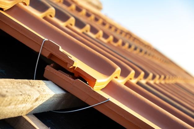 建設中の住宅の屋根を覆う木の板に取り付けられた黄色のセラミック屋根瓦を設置するための金属モンタージュアンカーのクローズアップ。