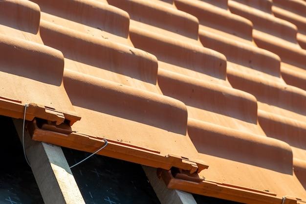 Крупным планом металлический монтажный анкер для установки желтой керамической черепицы, установленной на деревянных досках, покрывающих крышу строящегося жилого дома.