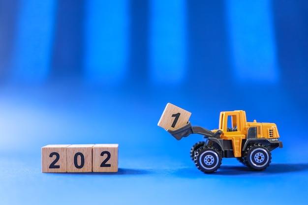 미니 트럭 장난감 자동차의 근접 촬영은 파란색 배경의 나무 번호 2021 블록을 밀어 올립니다
