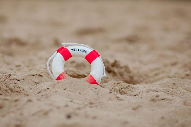 ビーチで砂を掘るミニチュア救命浮輪のクローズアップ。