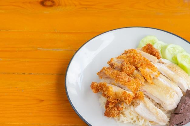 나무 탁자에 오이와 함께 튀긴 치킨 라이스와 찐 치킨 라이스의 근접 촬영