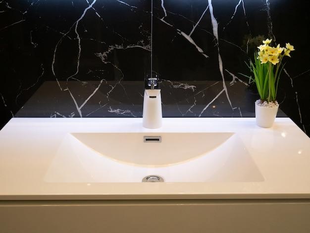 Крупный план современной ванной комнаты чисто белый умывальник с хромированным краном и ваза с цветами