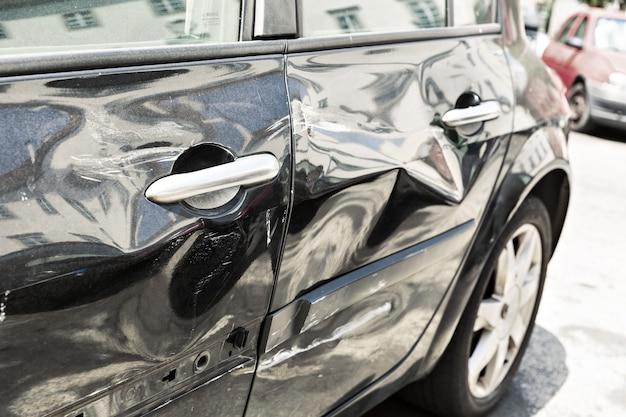 へこみのある現代の黒い車のクローズアップ