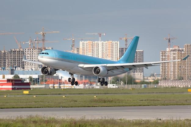 Крупным планом современный пассажирский самолет, готовый к посадке на взлетно-посадочную полосу в аэропорту летом.
