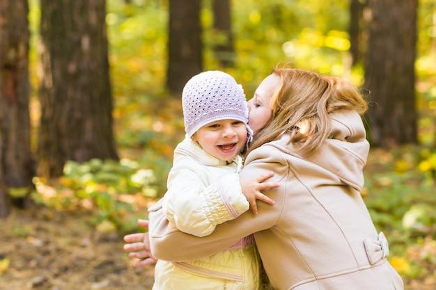 秋の公園で母と娘のクローズアップ。