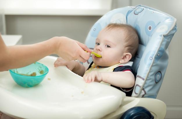スプーンから赤ちゃんにお粥を与える母親のクローズアップ