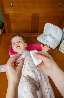 赤ちゃんの目をきれいにするために綿に生理血清を注ぐ母親の手のクローズアップ