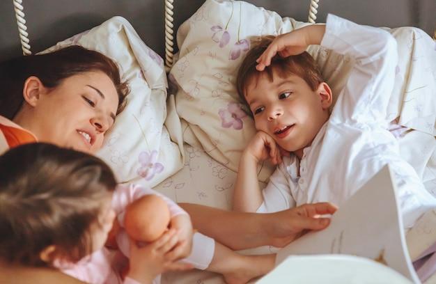 ベッドに横たわっている娘と息子の子供たちに物語の本を読んでいる母親のクローズアップ。週末の家族の余暇の時間の概念。