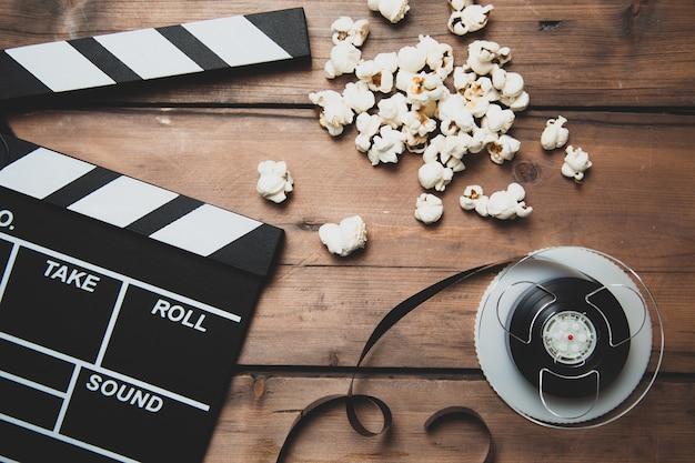 木の上のフィルムリールカチンコとポップコーンと映画用カメラのクローズアップ