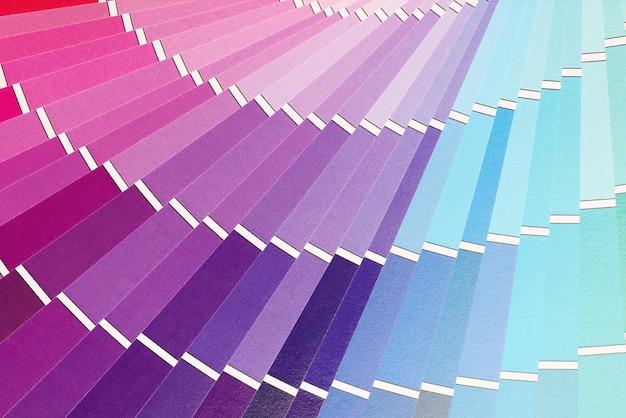 色見本の背景を持つ多色パレットのクローズアップ