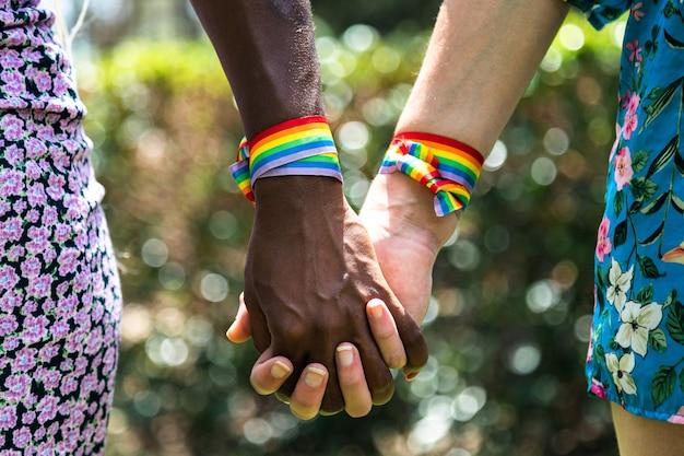 ぼやけた背景lgbtコンセプト愛と手をつないでいる多民族のレズビアンカップルのクローズアップ