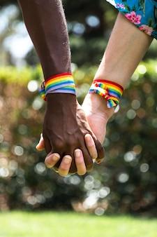 ぼやけた背景と手をつないでいる多民族のレズビアンカップルのクローズアップ垂直lgbt愛