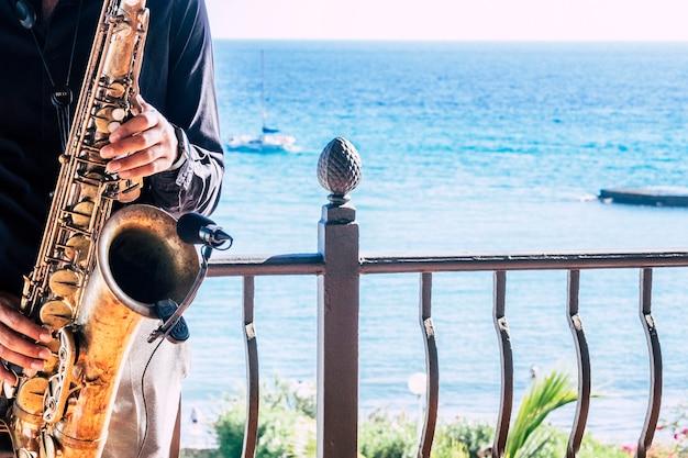 해변이나 바다 또는 바다와 레스토랑이나 바에서 자신의 악기를 만지고 음악 아티스트 색소폰의 근접 촬영