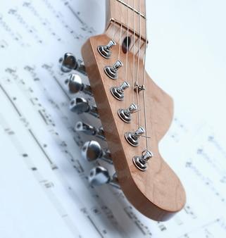 楽譜と白黒のエレキギターのクローズアップ。白い背景に分離。コピースペース付きの写真。