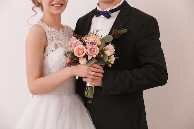 白い壁にウェディングブーケを保持している新婚夫婦のクローズアップ