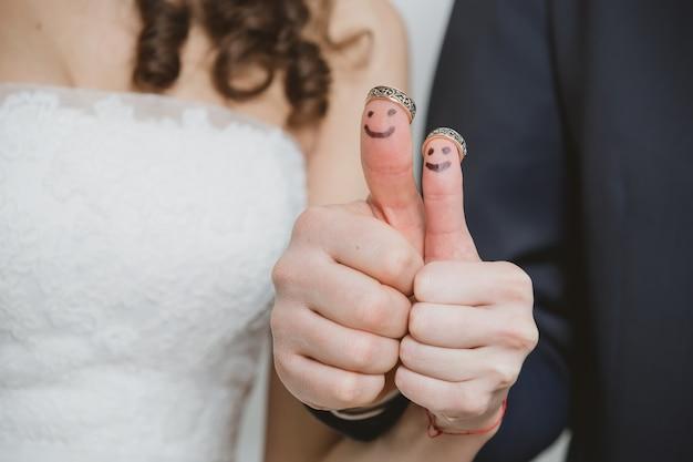 Крупным планом молодожены нарисованы на пальцах