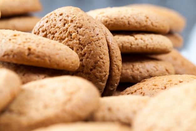 カロリーがあまり高くないオートミールクッキーのクローズアップ、あまり甘くない乾燥したカリカリのクッキー、オートミールで焼いた多孔質クッキー