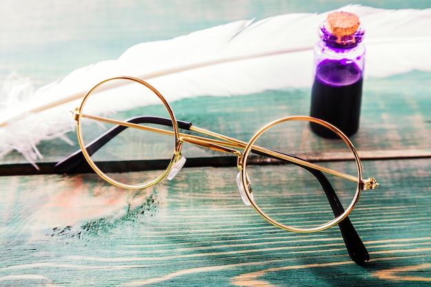 Крупным планом старые очки возле гусиное перо и чернильница на зеленый деревянный стол