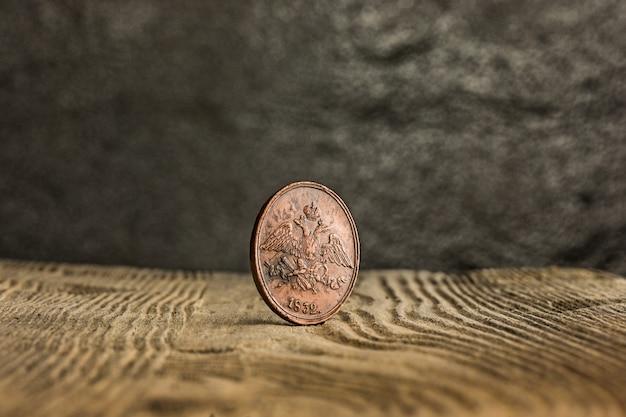 Крупный план старой русской монетки на деревянном столе.