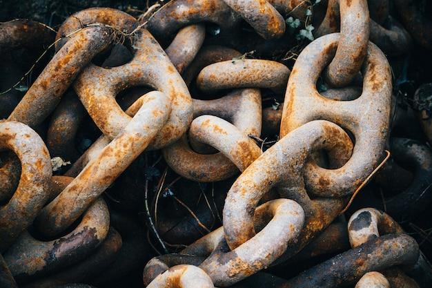 Крупным планом старые ржавые металлические цепи под огнями
