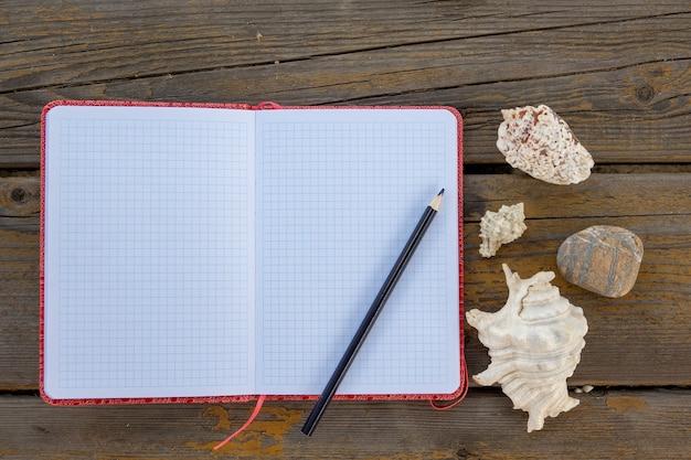 古い木の板のテクスチャの本と鉛筆のクローズアップ