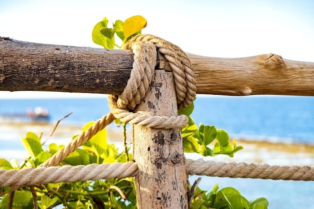 布ロープと緑の植生で覆われた古い木製の柵のクローズアップ。