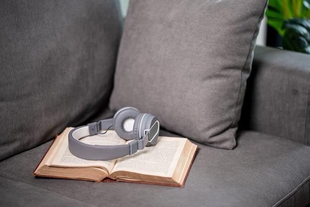 집에서 소파에 헤드폰을 끼고 열린 책 클로즈업