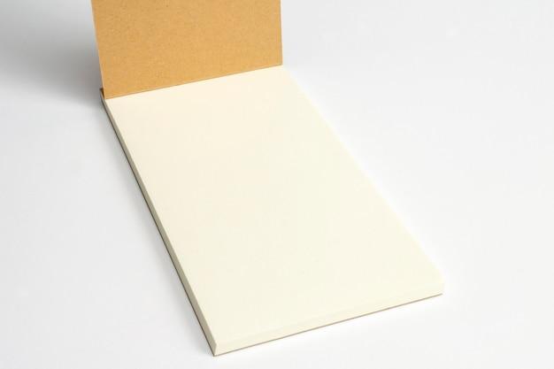 段ボールのハードカバーと白で隔離される空白のページで開かれた日記のクローズアップ。