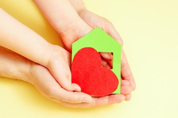 Крупный план бумажного красного сердца и красного сердца в руках ребенка и папы на желтом фоне. концепция семейного жилья.