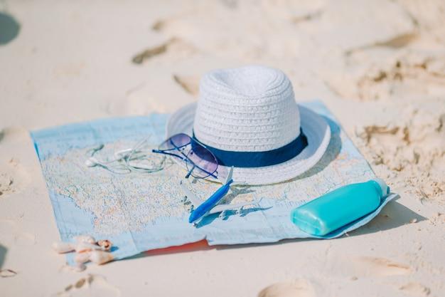 パスポート、おもちゃの飛行機、地図上のサングラスのクローズアップ