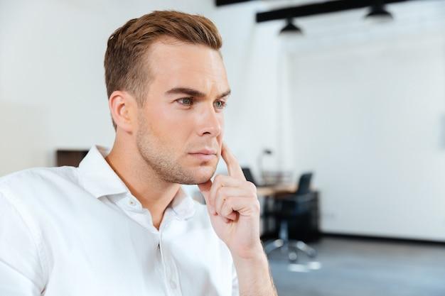 Крупным планом задумчивый молодой бизнесмен сидит и думает в офисе