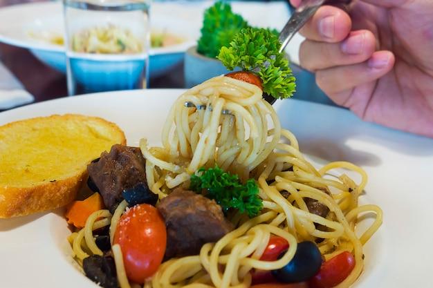 Крупным планом люди едят бекон спагетти