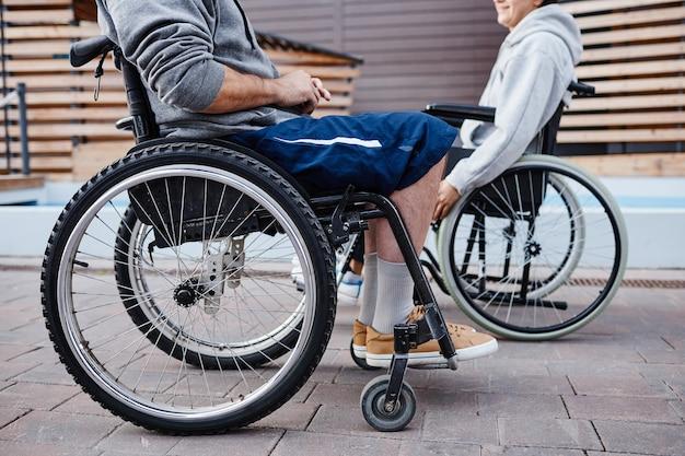 휠체어에 앉아 서로 이야기하며 시간을 보내는 장애가 있는 사람들의 클로즈업...