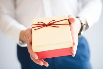 Closeup of person giving big gift box with bow