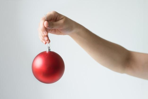Крупным планом лицо руки, держащей красный елочный шар